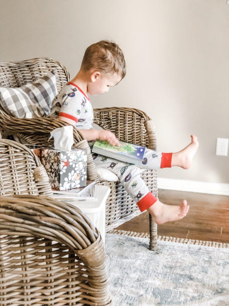 Little boy reading his bible in wicker chair