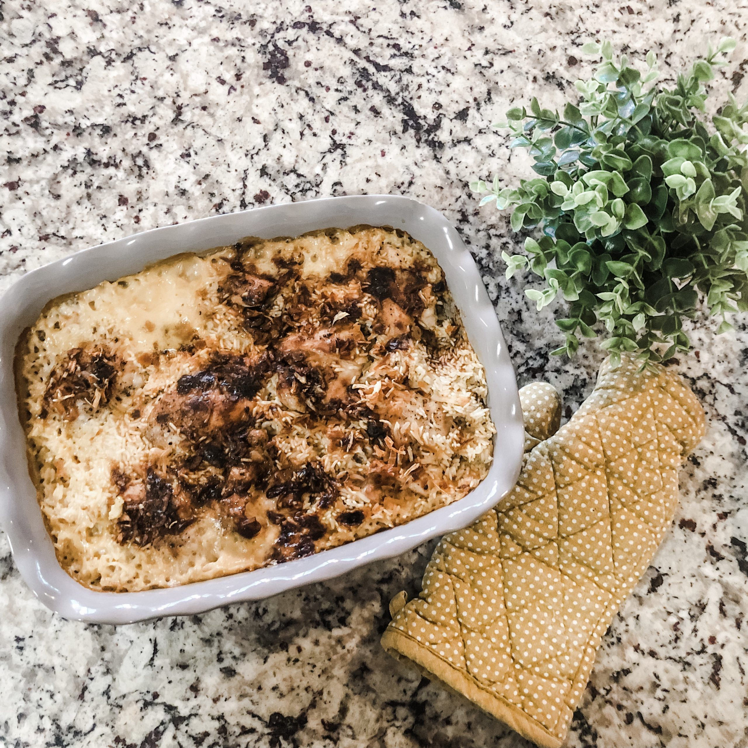 Baked chicken and rice in pan with greenery and oven mitt