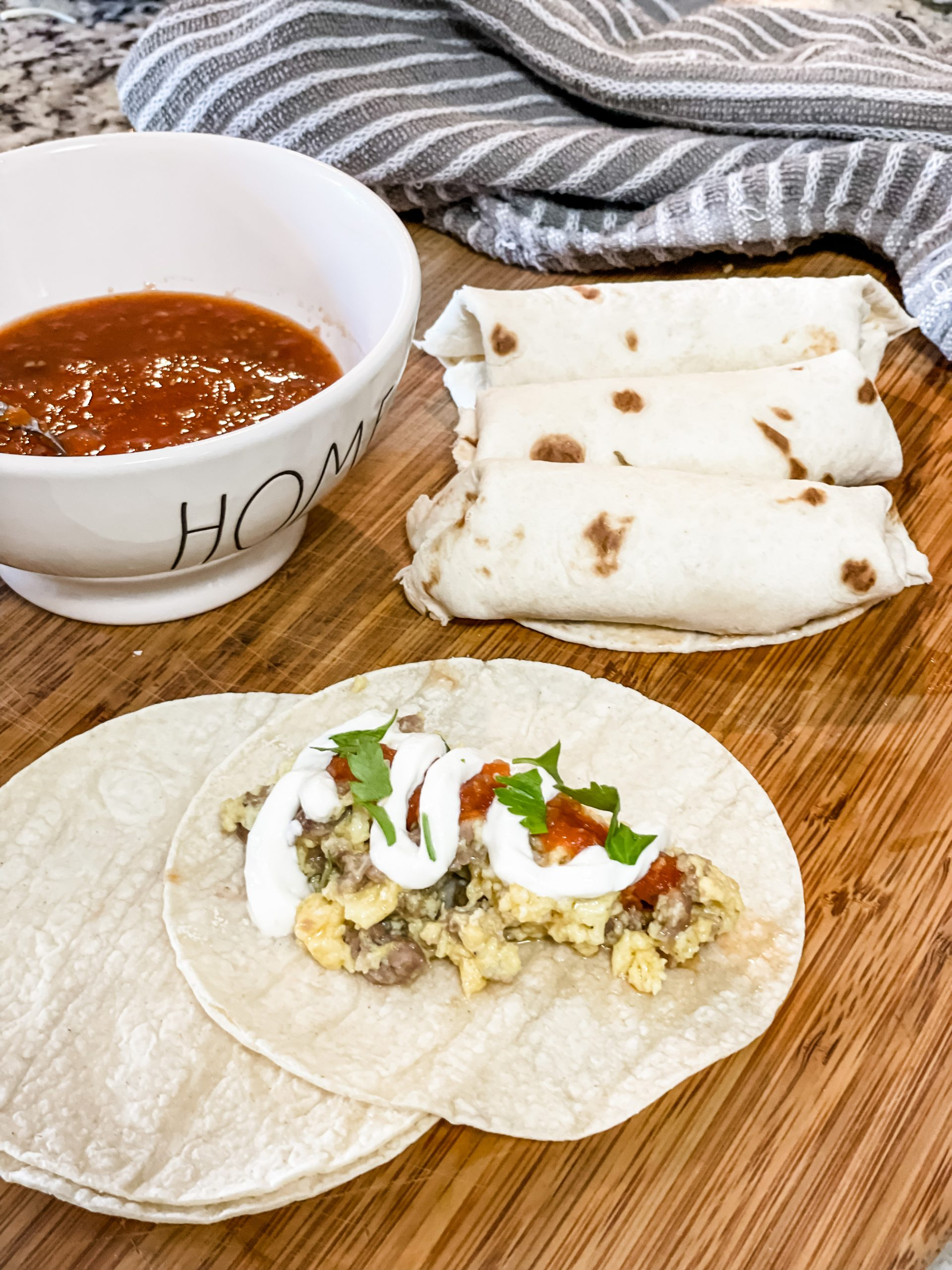 Sausage egg and cheese burrito topped with sour cream, salsa and cilantro on a wood cutting board