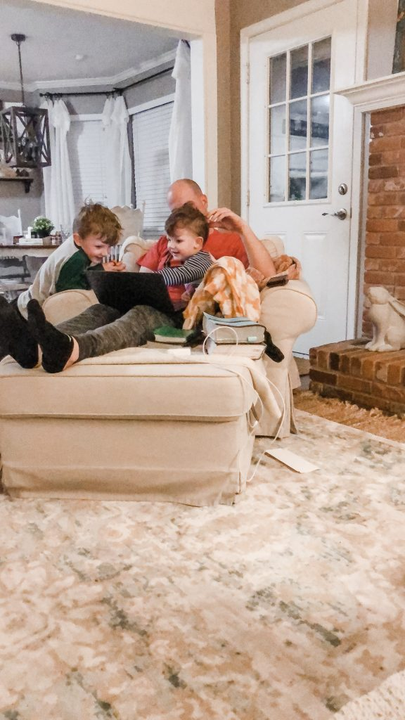 Two boys sitting with dad in large chair for fun devotions