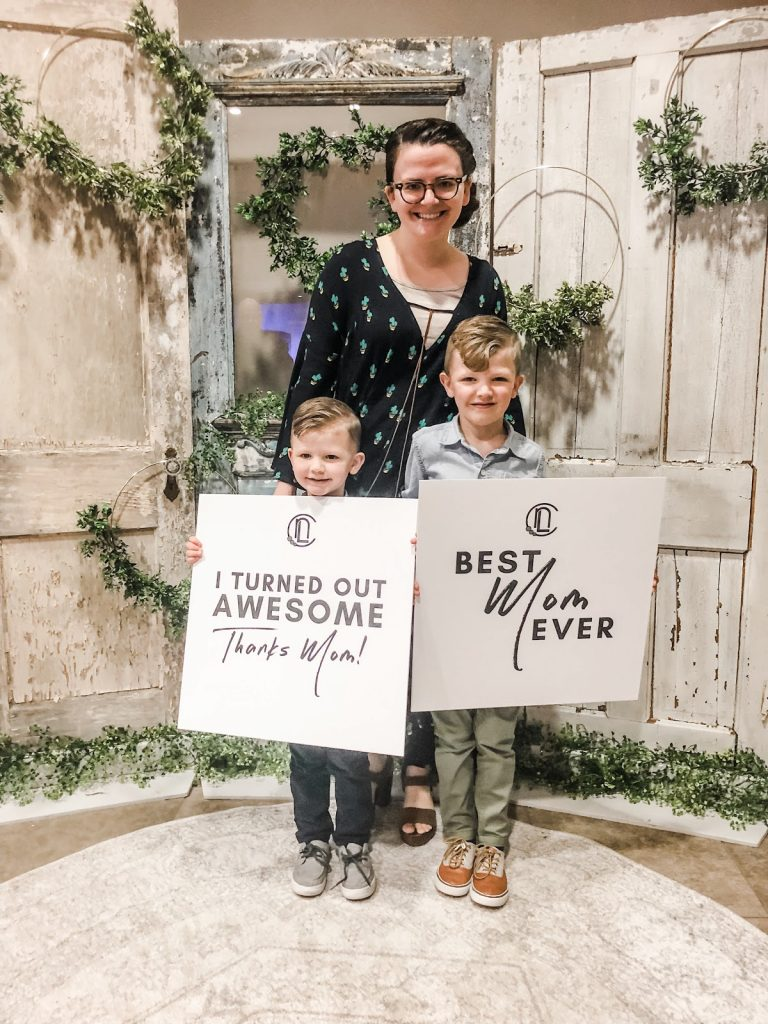 Mother standing with two sons holding signs that say Best Mom
