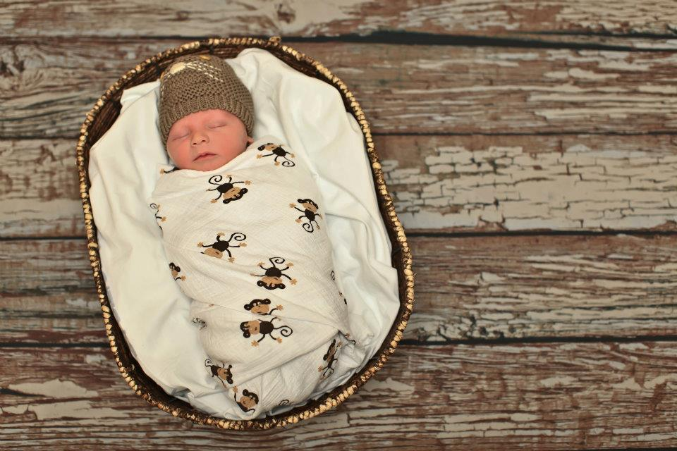 baby swaddled in small basket laying on wood floor