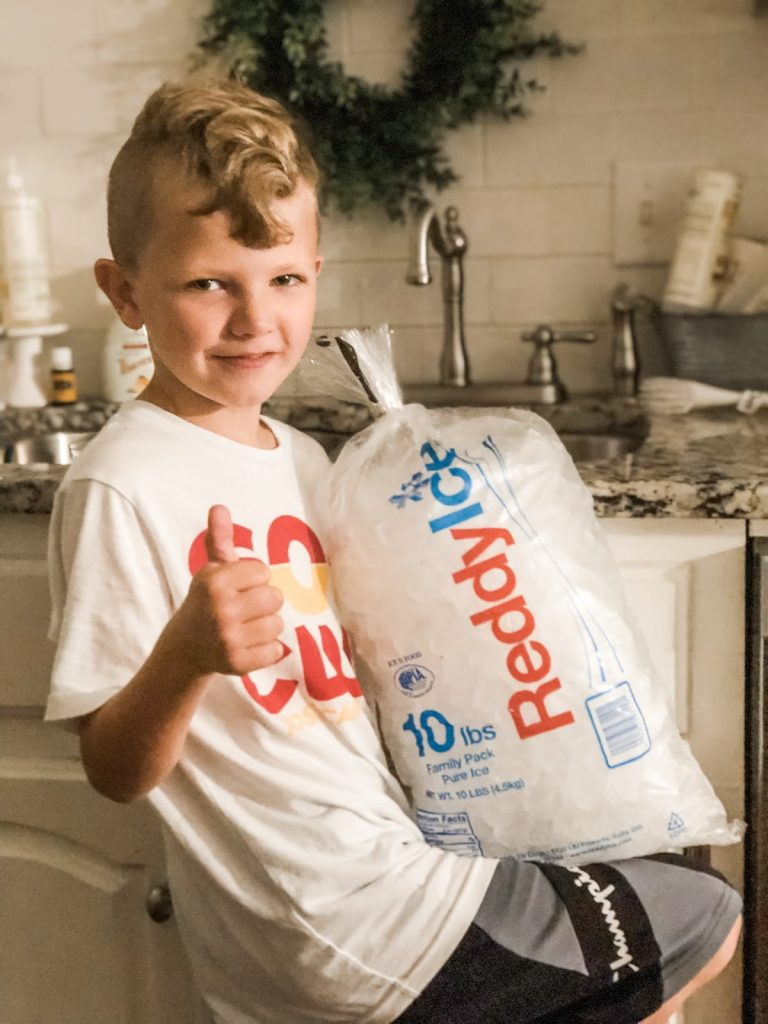 Small boy holding a bag of ice with a thumbs up after purchasing it on his own