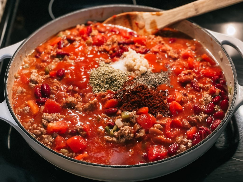 classic chili simmering on stove with spices added on top