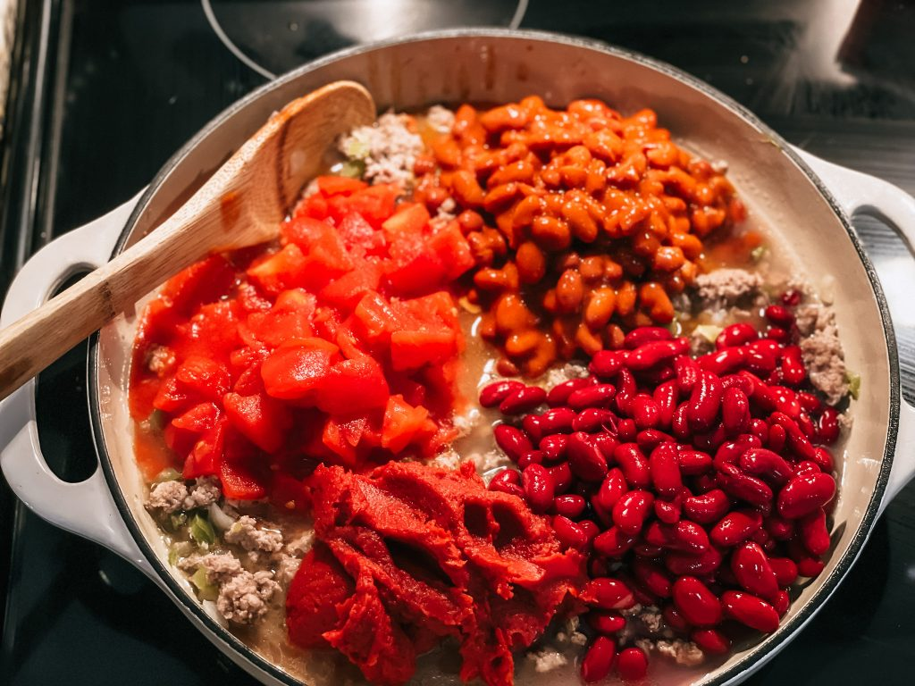 pan on stove with chili beans and tomatoes being added in