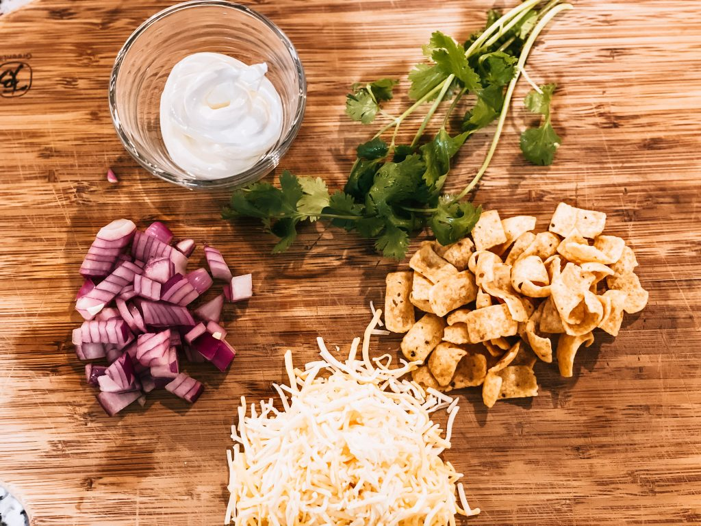 chili toppings spread on wooden cutting board for serving
