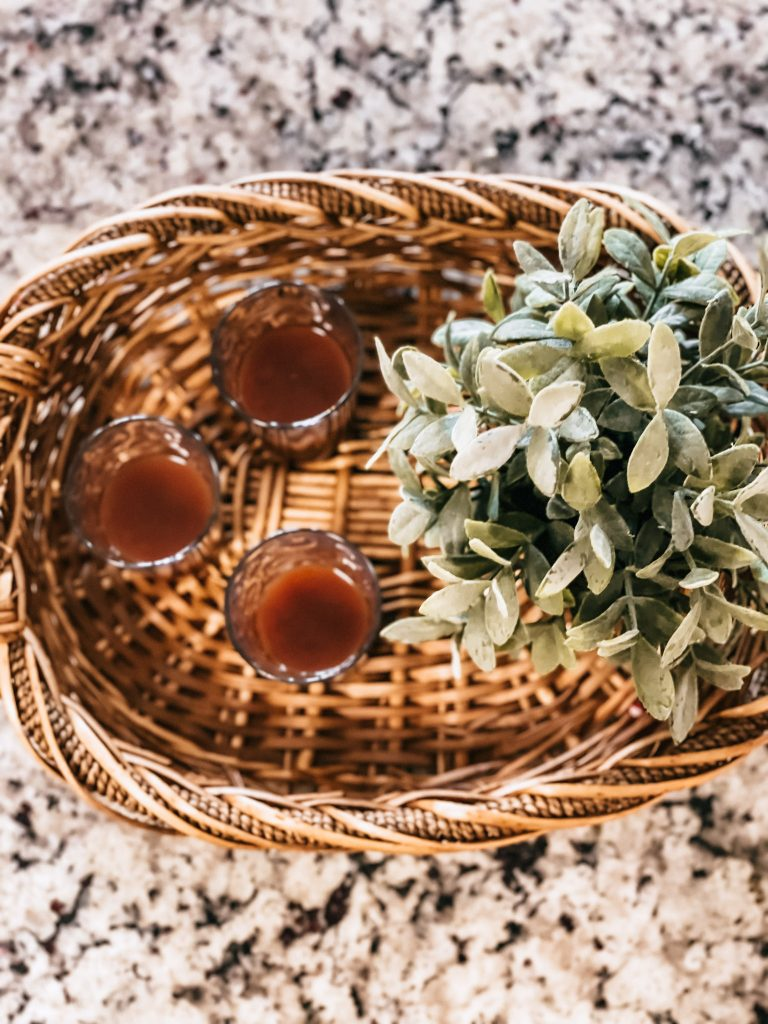 three immune boosting wellness drinks on basket tray with plant