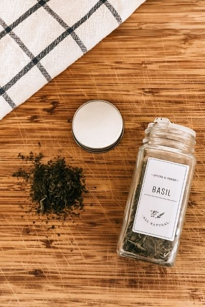 preserved herbs on cutting board with spice jar and kitchen towel