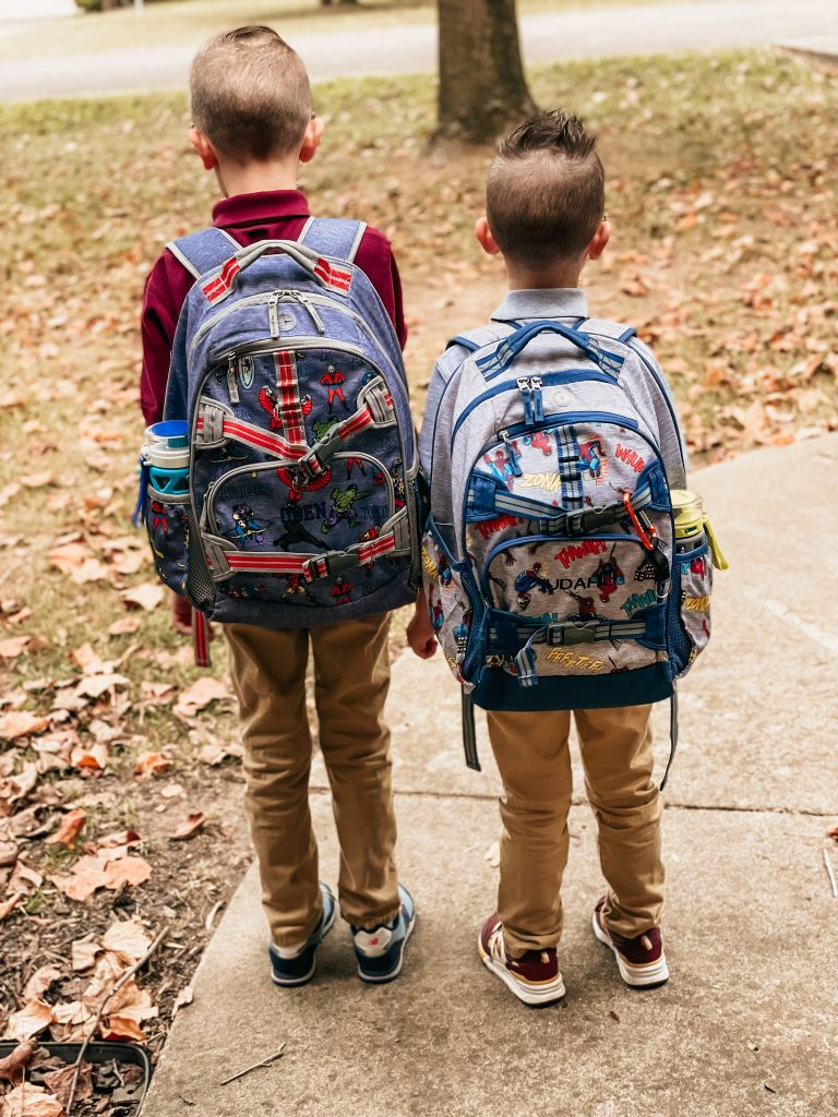 two boys with backpacks on ready for school