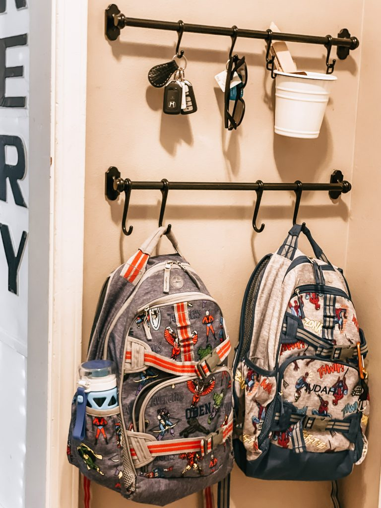 two backpacks hanging on hooks for school routines