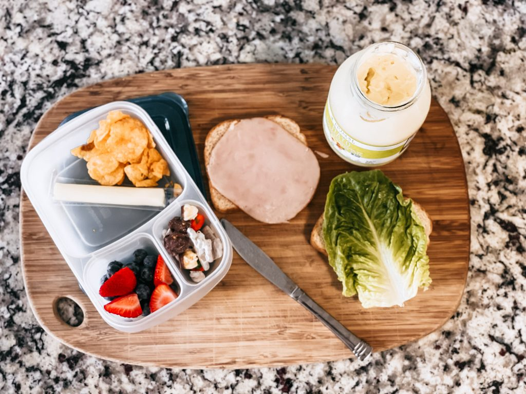 school lunchbox and sandwich fixings on cutting board